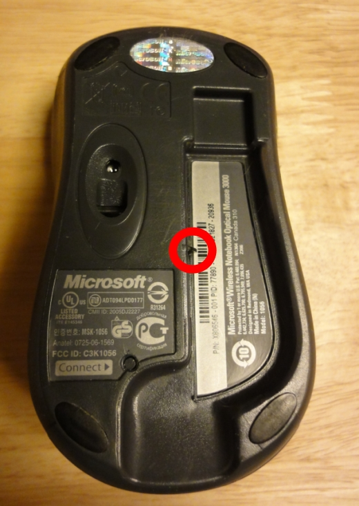 The button was stuck, fooling the mouse into thinking that the receiver was docked. This explained why the red light was off.