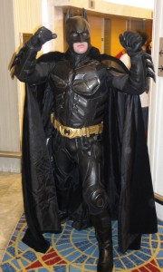 Batman stands with his arms up, showing off his armor and cape.