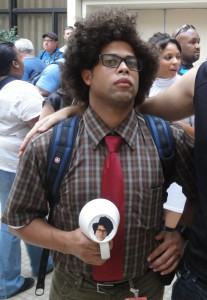Maurice Moss from The IT Crowd, holding his famous cup. The wedge in his hair is clearly visible.