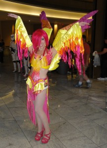 A girl in a phoenix costume stands with her arms raised, allowing her wings to hang. The costume is a vibrant mix of yellow, orange, and red plummage. A smaller phoenix can be found on her chest, with its wings extended.