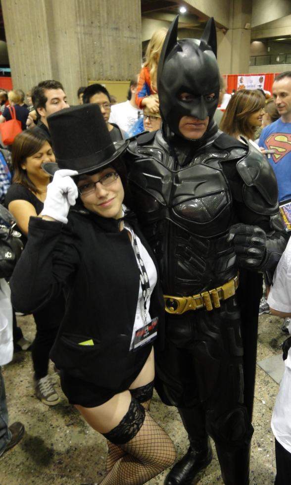 Batman stands next to a girl with a top hat.