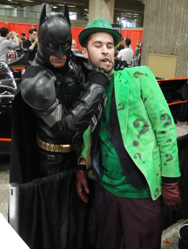 Batman punches the Riddler in the chin, with the old batmobile in the background.