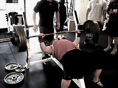A guy bench pressing at a gym, with a spotter behind him. I didn't have a spotter, but this picture captures the general mood of a gym.
