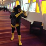 Cyclops from X-men taking a photo. Black and yellow costume, no blue.
