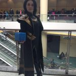 A female Loki holding the Tesseract in her right hand.