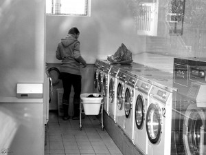 A woman stands in a laundry facility with her back turned. Black and white photo.