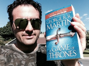 Matt Refghi standing outside with sunglasses and a paperback copy of George R.R. Martin's A Game of Thrones.