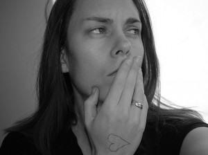 A woman deep in thought, with her hand over her mouth, slightly. She looks to the right, with a slight frown.