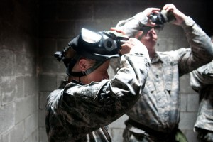 US Army soldiers removing their gas masks as part of a drill